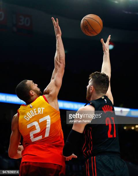 Jusuf Nurkic of the Portland Trail Blazers lays up the ball against Rudy Gobert of the Utah Jazz at Moda Center on April 11 2018 in Portland...