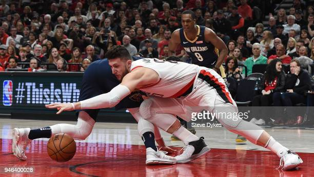 Jusuf Nurkic of the Portland Trail Blazers scrambles for a ball with Nikola Mirotic of the New Orleans Pelicans as Rajon Rondo looks on during the...