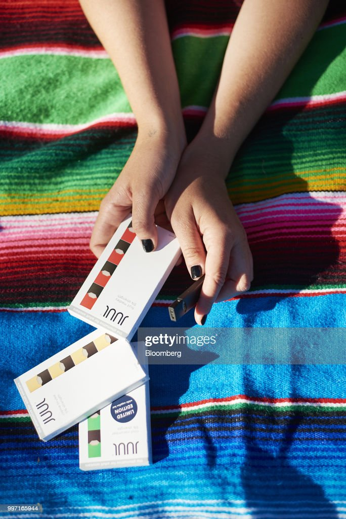 A Juul Labs Inc. e-cigarette and flavored pods are arranged for a photograph in the Brooklyn Borough of New York, U.S., on Sunday July 8, 2018. Juul Labs, the maker of the popular e-cigarette brand that has recently come under fire from health officials over its popularity with young adults, plans to introduce a line of lower-nicotine pods. The company will begin to sell pods with a 3-percent nicotine concentration in its mint and Virginia tobacco flavors later this year, according to a statement Thursday. Photographer: Gabby Jones/Bloomberg via Getty Images