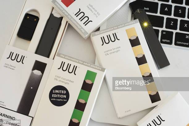 A Juul Labs Inc ecigarette USB charger and flavored pods are arranged for a photograph in the Brooklyn Borough of New York US on Sunday July 8 2018...