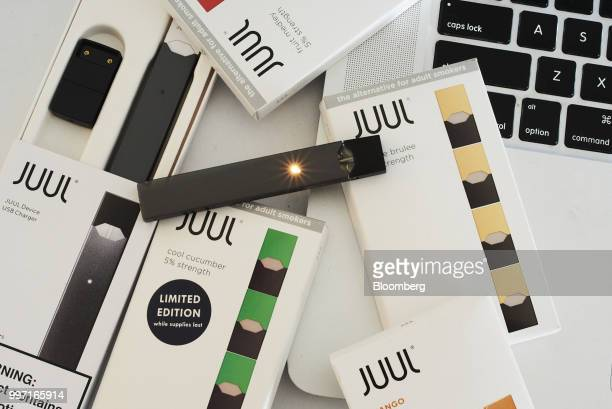 Juul Labs Inc. E-cigarette, USB charger, and flavored pods are arranged for a photograph in the Brooklyn Borough of New York, U.S., on Sunday July 8,...