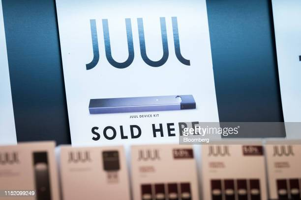 Juul Labs Inc. Signage is displayed behind packages of device kits and pods at a store in San Francisco, California, U.S., on Tuesday, June 25, 2019....