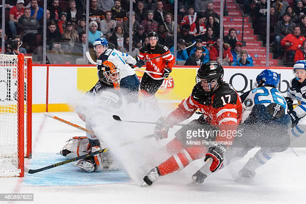 Juuse Saros of Team Finland gets some ice spray from Connor McDavid of Team Canada during the 2015 IIHF World Junior Hockey Championship game at the...