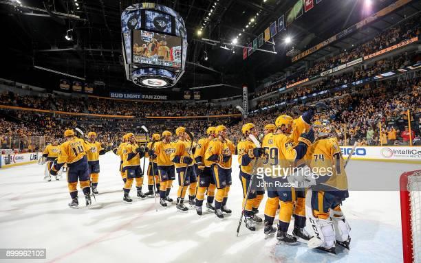 Juuse Saros of the Nashville Predators celebrates a 30 win with his teammates against the Minnesota Wild during an NHL game at Bridgestone Arena on...