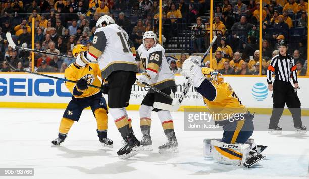 Juuse Saros of the Nashville Predators deflects a shot off his mask as James Neal and Erik Haula of the Vegas Golden Knights provide a screen during...