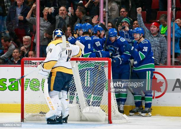 Juuse Saros of the Nashville Predators looks on dejected as Loui Eriksson of the Vancouver Canucks is congratulated by teammates after scoring during...