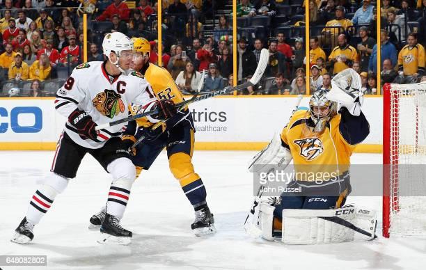 Juuse Saros of the Nashville Predators makes a glove save against Jonathan Toews of the Chicago Blackhawks during an NHL game at Bridgestone Arena on...