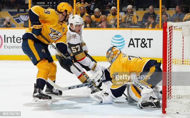 Juuse Saros of the Nashville Predators makes the save against David Perron of the Vegas Golden Knights as Roman Josi defends during an NHL game at...