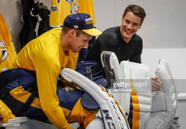 Juuse Saros shares a laugh with Pekka Rinne of the Nashville Predators as they dress for warmups prior to an NHL game against the Chicago Blackhawks...