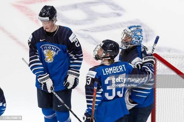 Juuso Parssinen, Brad Lambert and goaltender Kari Piiroinen of Finland celebrate their victory over Germany during the 2021 IIHF World Junior...