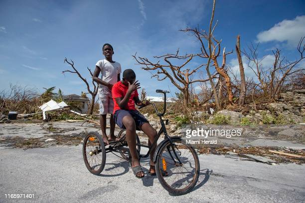 Juvence Davlmay left, and cousin Rodney Dorvilus look at the destruction from Hurricane Dorian at Marsh Harbour in Great Abaco Island, Bahamas on...