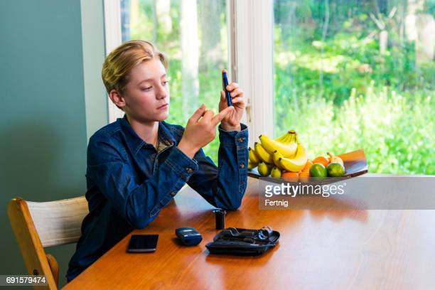 Juvenile diabetes patient checking his blood glucose levels at home