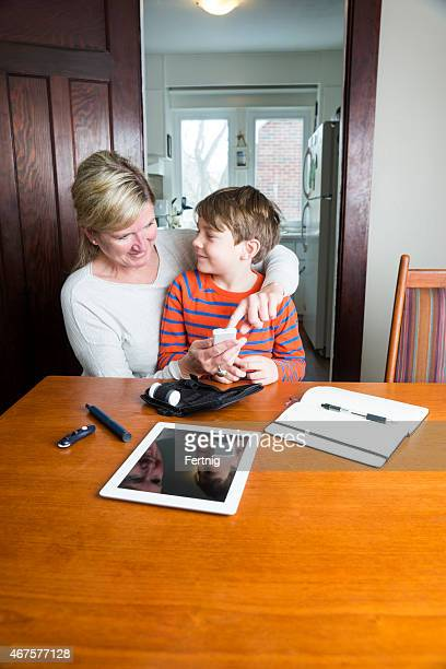 Juvenile diabetic patient testing blood sugar with his mother