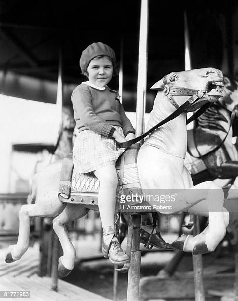 Juvenile Girl Wearing A Dress Wool Sweater & Tam Riding A White Carousal Horse Smiling Saddle Stirrups.
