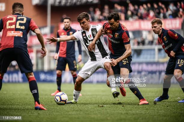 Juventus' Argentine forward Paulo Dybala and Genoa's Serbian midfielder Ivan Radovanovic go for the ball during the Italian Serie A football Match...