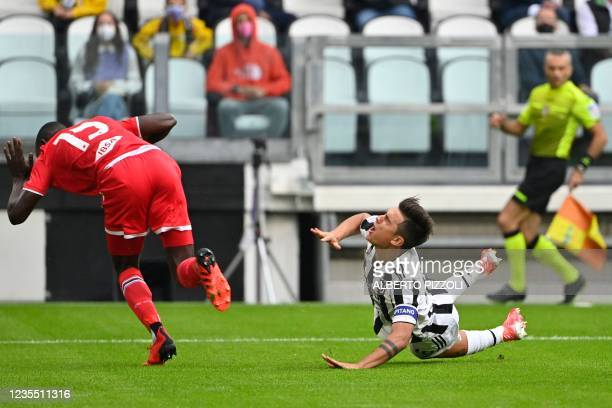 Juventus' Argentine forward Paulo Dybala and Sampdoria's Gambian defender Omar Colley fall after colliding during the Italian Serie A football match...