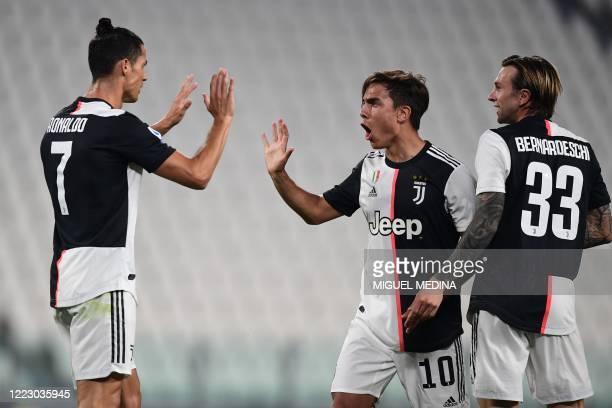 Juventus' Argentine forward Paulo Dybala celebrates with Juventus' Portuguese forward Cristiano Ronaldo and Juventus' Italian forward Federico...
