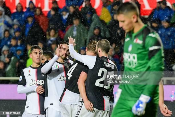 Juventus' Argentine forward Paulo Dybala celebrates with teamates after scoring during the Italian Serie A football match Atalanta Bergamo vs...