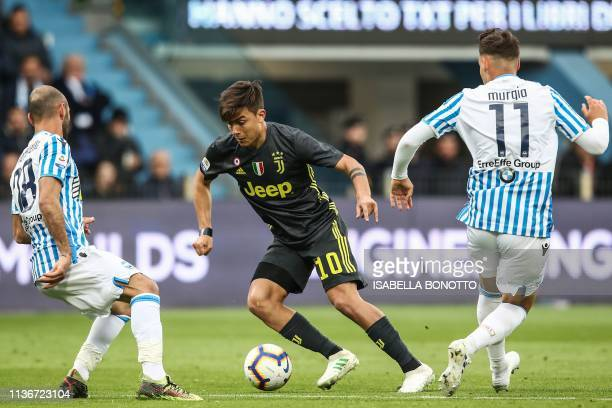 Juventus' Argentine forward Paulo Dybala challenges SPAL's Italian midfielder Pasquale Schiattarella and SPAL's Italian midfielder Alessandro Murgia...