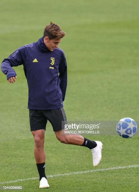 Juventus' Argentine forward Paulo Dybala controls a ball during a training session on the eve of the UEFA Champions League group H football match...