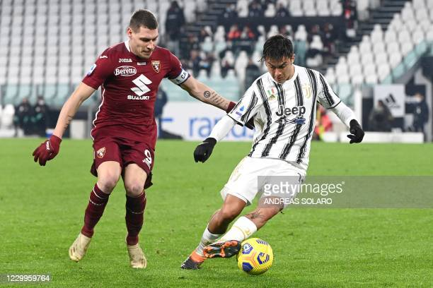 Juventus' Argentine forward Paulo Dybala fights for the ball with Torino's Italian forward Andrea Belotti during the Italian Serie A football match...
