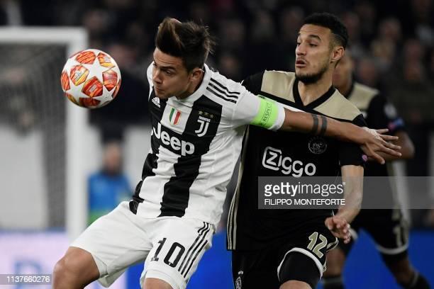 Juventus' Argentine forward Paulo Dybala holds off Ajax's Dutch defender Noussair Mazraoui during the UEFA Champions League quarterfinal second leg...