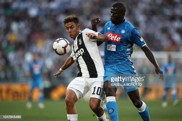 Juventus' Argentine forward Paulo Dybala holds off Napoli's Senegalese defender Kalidou Koulibaly during the Italian Serie A football match Juventus...