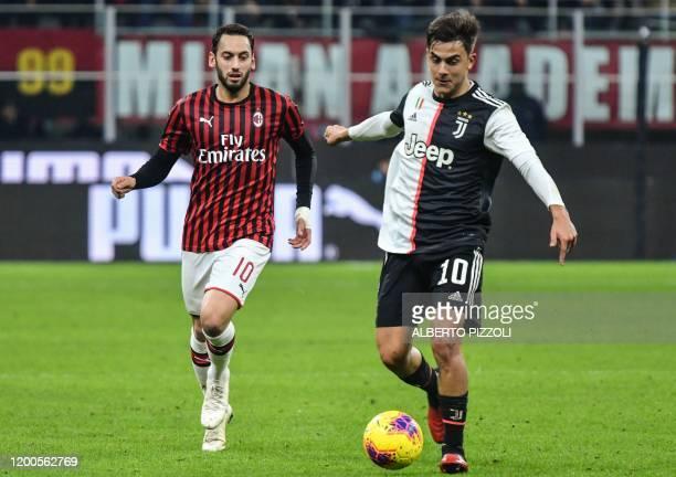 Juventus' Argentine forward Paulo Dybala outruns AC Milan's Turkish forward Hakan Calhanoglu during the Italian Cup semifinal first leg football...