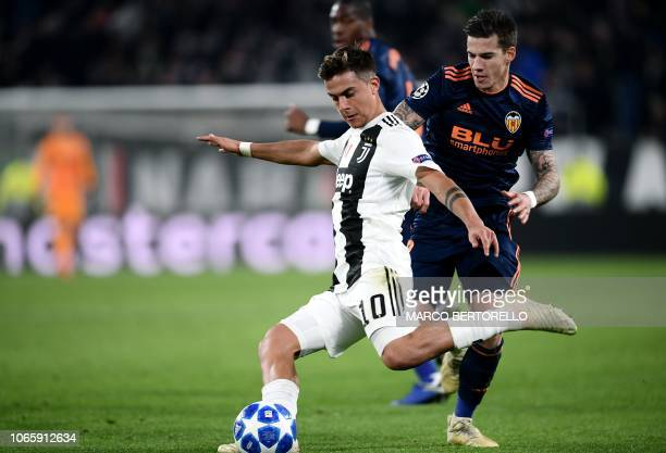 Juventus' Argentine forward Paulo Dybala shoots on goal despite Valencia's Spanish forward Santi Mina during the UEFA Champions League group H...