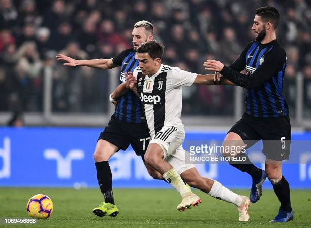 Juventus' Argentine forward Paulo Dybala vies for the ball with Inter Milan's Croatian midfielder Marcelo Brozovic and Inter Milan's Italian...