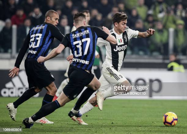 Juventus' Argentine forward Paulo Dybala vies for the ball with Inter Milan's Brazilian defender Joao Miranda and Inter Milan's Slovak defender Milan...