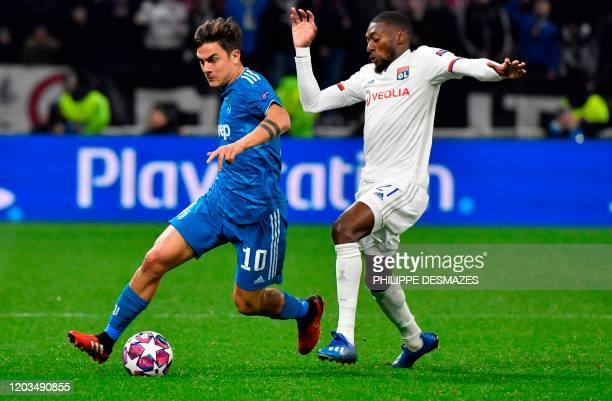 Juventus' Argentine forward Paulo Dybala vies for the ball with Lyon's French forward Karl Toko Ekambi during the UEFA Champions League round of 16...