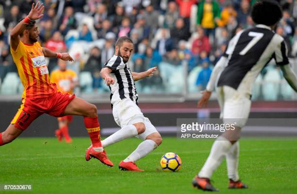 Juventus' Argentinian forward Gonzalo Gerardo Higuain fights for the ball with Benevento's Achraf Lazaar during the Italian Serie A football match...