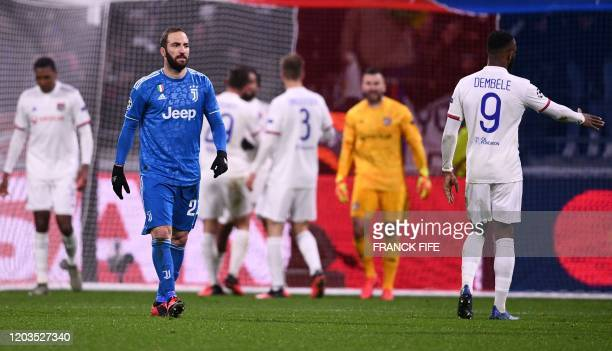Juventus' Argentinian forward Gonzalo Higuain and Lyon's French forward Moussa Dembele react during the UEFA Champions League round of 16 firstleg...