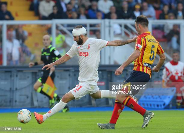 STADIUM LECCE PUGLIA ITALY Juventus' Argentinian forward Gonzalo Higuain banded after he suffered an injury kicks the ball next to Lecce's Italian...