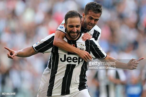 Juventus' Argentinian forward Gonzalo Higuain celebrates with Bosnian-Herzegovinian midfielder midfielder Miralem Pjanic after scoring a goal during...
