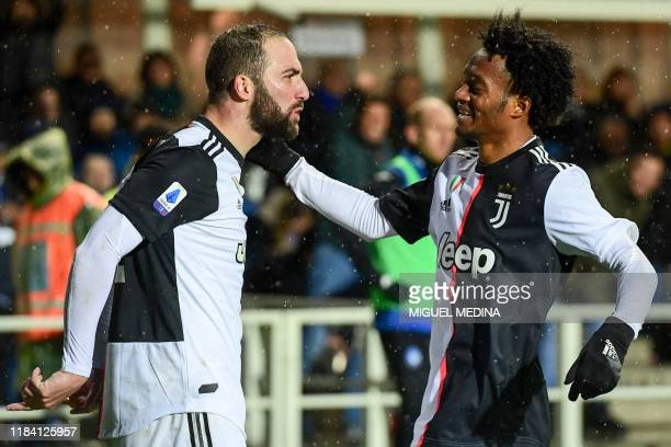 Juventus' Argentinian forward Gonzalo Higuain celebrates with Juventus' Colombian midfielder Juan Cuadrado after scoring his second goal during the...