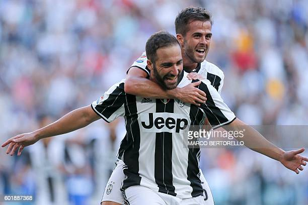 Juventus' Argentinian forward Gonzalo Higuain celebrates with teammate Argentinian forward Paulo Dybala after scoring a goal during the Italian Serie...