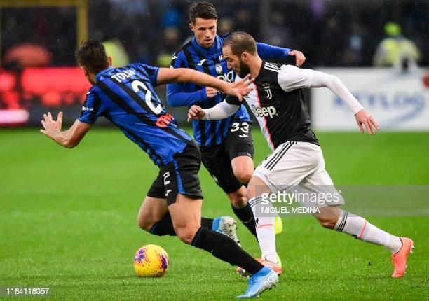 Juventus' Argentinian forward Gonzalo Higuain challenges Atalanta's Brazilian defender Rafael Toloi and Atalanta's Dutch defender Hans Hateboer...
