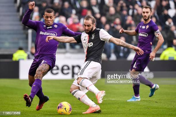 Juventus' Argentinian forward Gonzalo Higuain challenges Fiorentina's Brazilian defender Igor Julio during the Italian Serie A football match...
