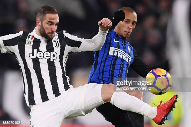 Juventus' Argentinian forward Gonzalo Higuain fights for the ball with Inter Milan's Brazilian defender Joao Miranda de Souza Filho during the...