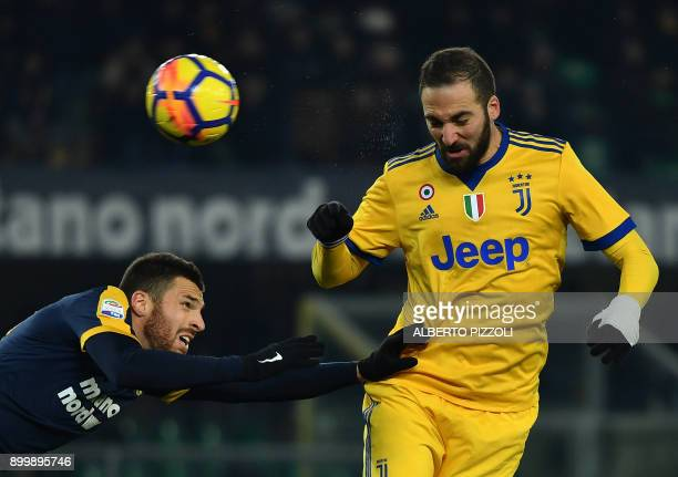 TOPSHOT Juventus' Argentinian forward Gonzalo Higuain fights for the ball with Hellas Verona's French defender Thomas Heurtaux during the Italian...