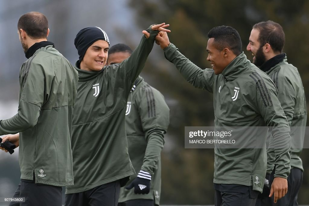 Juventus' Argentinian forward Paulo Dybala (L) and Juventus' Brazilian defender Alex Sandro tap hands during a training session on the eve of the UEFA Champions League football match Tottenham Hotspur vs Juventus on March 6, 2018 at the Juventus training center in Vinovo. /