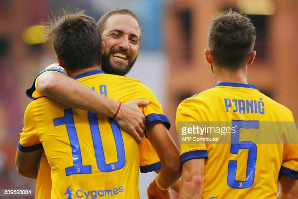 Juventus' Argentinian forward Paulo Dybala celebrates with compatriot forward Gonzalo Higuain after scoring during the Italian Serie A football match...