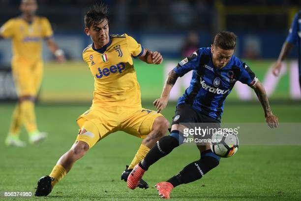 Juventus' Argentinian forward Paulo Dybala fights for the ball with Atalanta's Argentinian forward Papu Gomez during the Italian Serie A football...