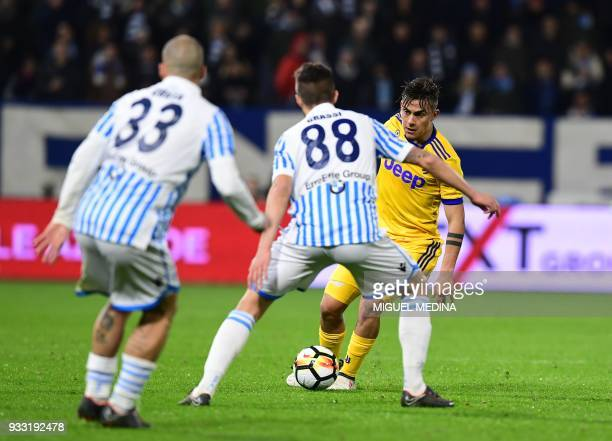 Juventus' Argentinian forward Paulo Dybala vies with Spal's Italian defender Filippo Costa and Spal's Italian midfielder Alberto Grassi during the...