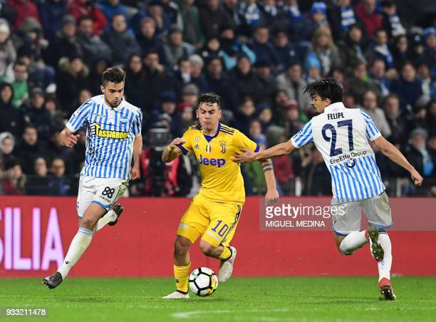 Juventus' Argentinian forward Paulo Dybala vies with Spal's Italian midfielder Alberto Grassi and Spal's Brazilian defender Felipe Dal Bello during...