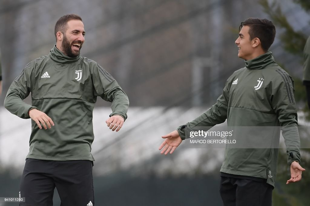 Juventus' Argentinian forwards, Gonzalo Higuain (L) and Paulo Dybala attend a training session on the eve of the UEFA Champions League football match Juventus vs Real Madrid on April 2, 2018 at the Juventus training center in Vinovo. /