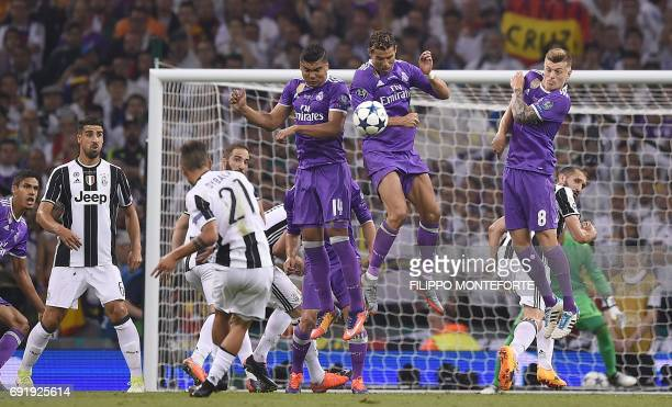 Juventus' Argentinian striker Paulo Dybala takes a free kick that strikes Real Madrid's Portuguese striker Cristiano Ronaldo during the UEFA...