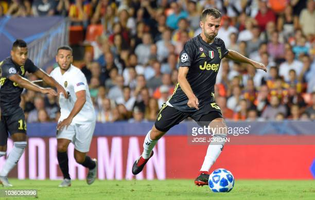 Juventus' Bosnian defender Miralem Pjanic kicks a penalty and scores during the UEFA Champions League group H football match between Valencia CF and...